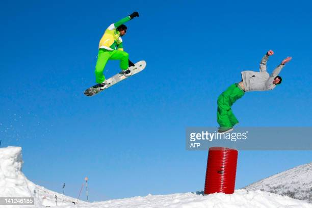 Snowboarders jumpand make acrobatic figures in the snowpark in the Val d'Ese ski resort in Bastelica close to Ajaccio in the French Mediterranean...