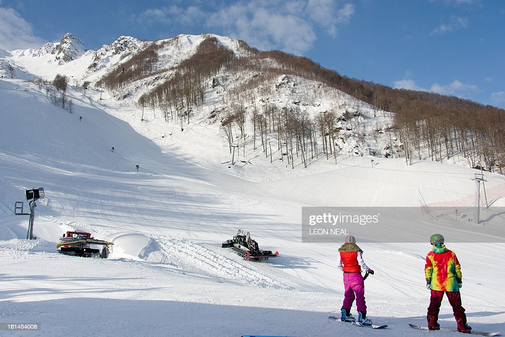 Snowboarders look up towards the peak of Mount Aigba in the 'Rosa Khutor' Extreme Park on February 11, 2013. With a year to go until the Sochi 2014 Winter Games, tests events and World Championship competitions are underway.