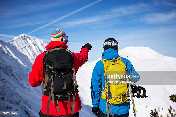 Snowboarders looking at view of snow-covered mountain