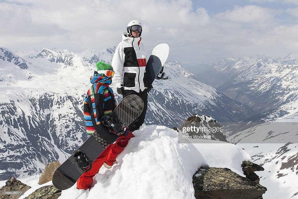 Snowboarders on rocky mountaintop : Stock Photo