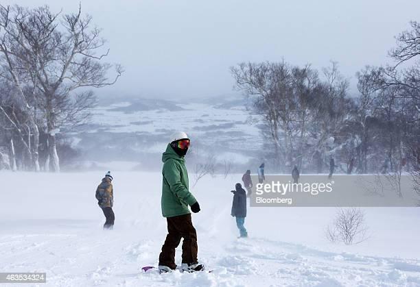 Snowboarders ride down a slope at the Niseko Hanazono resort operated by Nihon Harmony Resorts KK in Kutchan Hokkaido Japan on Sunday Feb 15 2015 The...