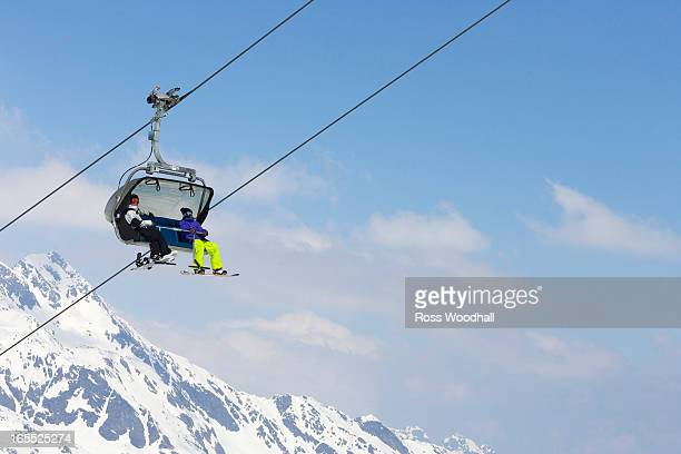 Snowboarders riding chair lift