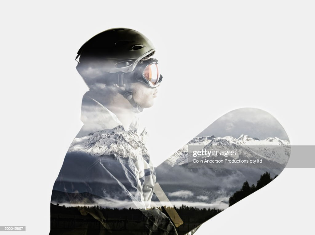 Snowboarder's silhouette in reflection of snowy mountains
