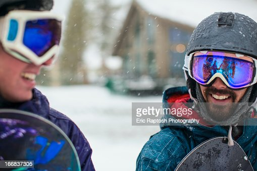 Snowboarders talking in snow