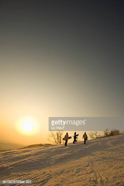 Snowboarders walking up slope at sunset