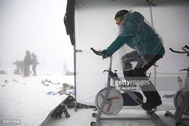 2014 Winter Olympics Australia Jarryd Hughes warming up on a stationary bike during weather delay before Men's Snowboard Cross Quarterfinals at Rosa...