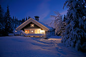 Cottage covered with snow and illuminated in the polar night.