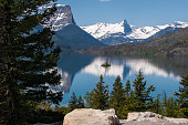 Snow capped mountain reflection body blue water. Small island pine trees