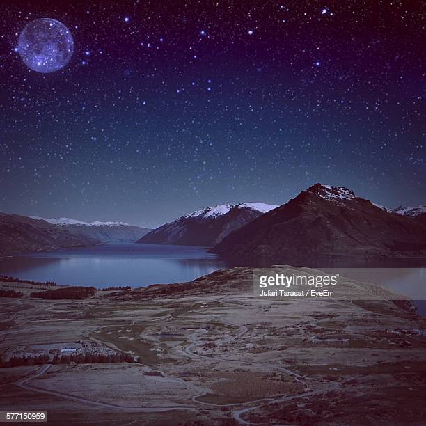 Snowcapped Mountains By Lake At Night