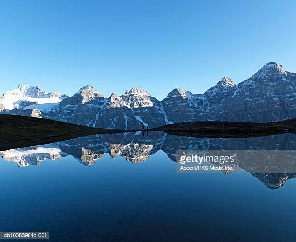 Snowcapped mountains reflecting in lake water, two hikers walking in distance