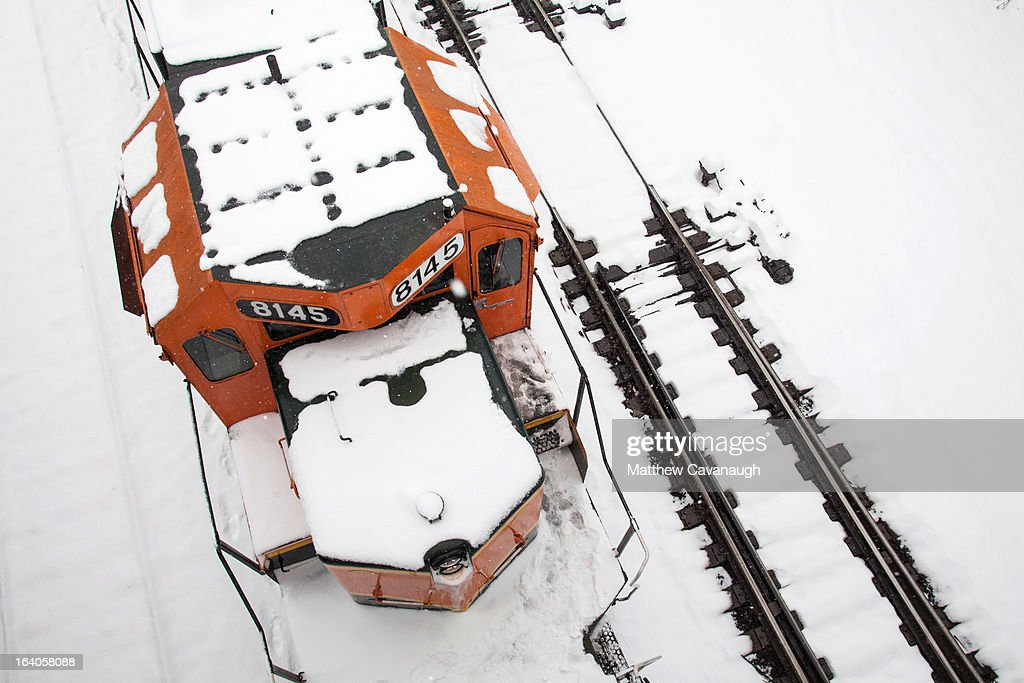 A snow-covered freight train is seen from a bridge above the rails on March 19, 2013 in Deerfield, Massachusetts. Another winter storm blew through the Northeast yesterday, with snow and sleet closing schools in some areas and making for a messy morning commute.