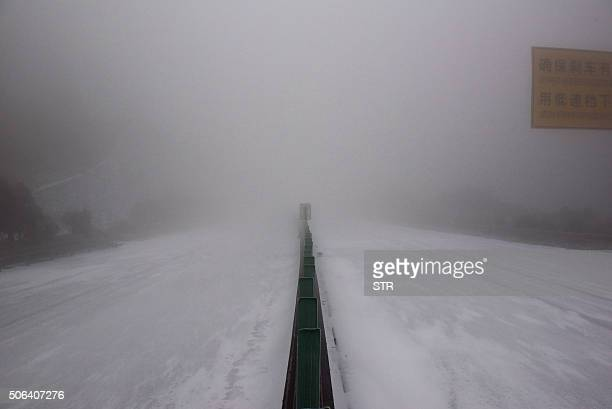 A snowcovered highway is temporarily closed during the cold snap in Shaoguan south China's Guangdong province on January 23 2016 Much of China...