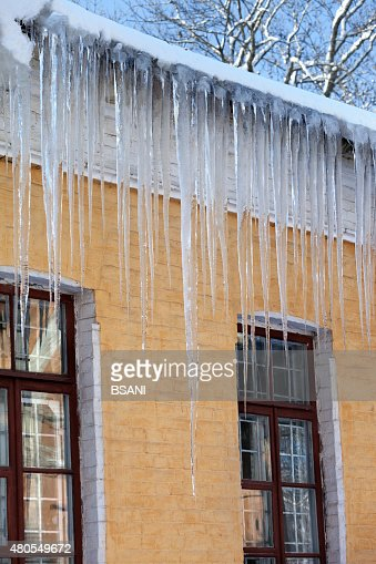 Snow-covered roof with big icicles in winter day : Stock Photo