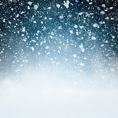 Fluffy snowflakes falling in front of a blue background with vignette - computer generated image