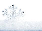 Snowflake in white snow.
