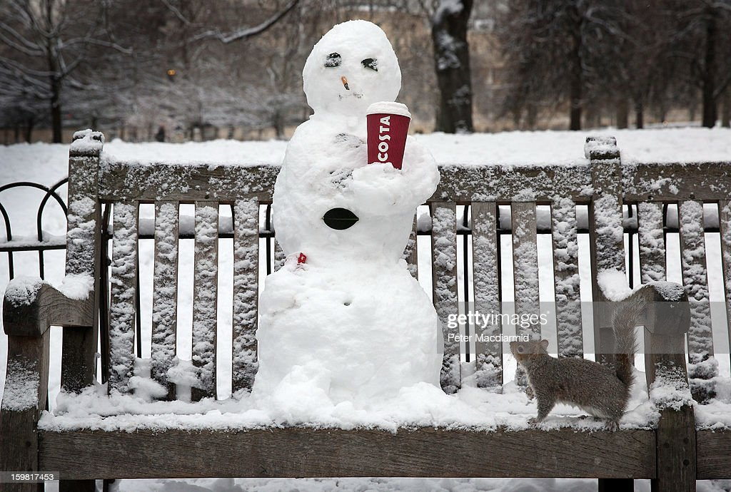 A snowman complete with cigarette and coffee cup is viewed by a squirrel in St James's Park on January 21, 2013 in London, England. The United Kingdom has suffered a weekend of heavy snowfall with many transport routes affected.