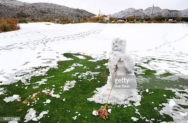 A snowman hitting a golf ball is seen on the course as snow and rain caused play to be suspended due to weather during the first round of the World...