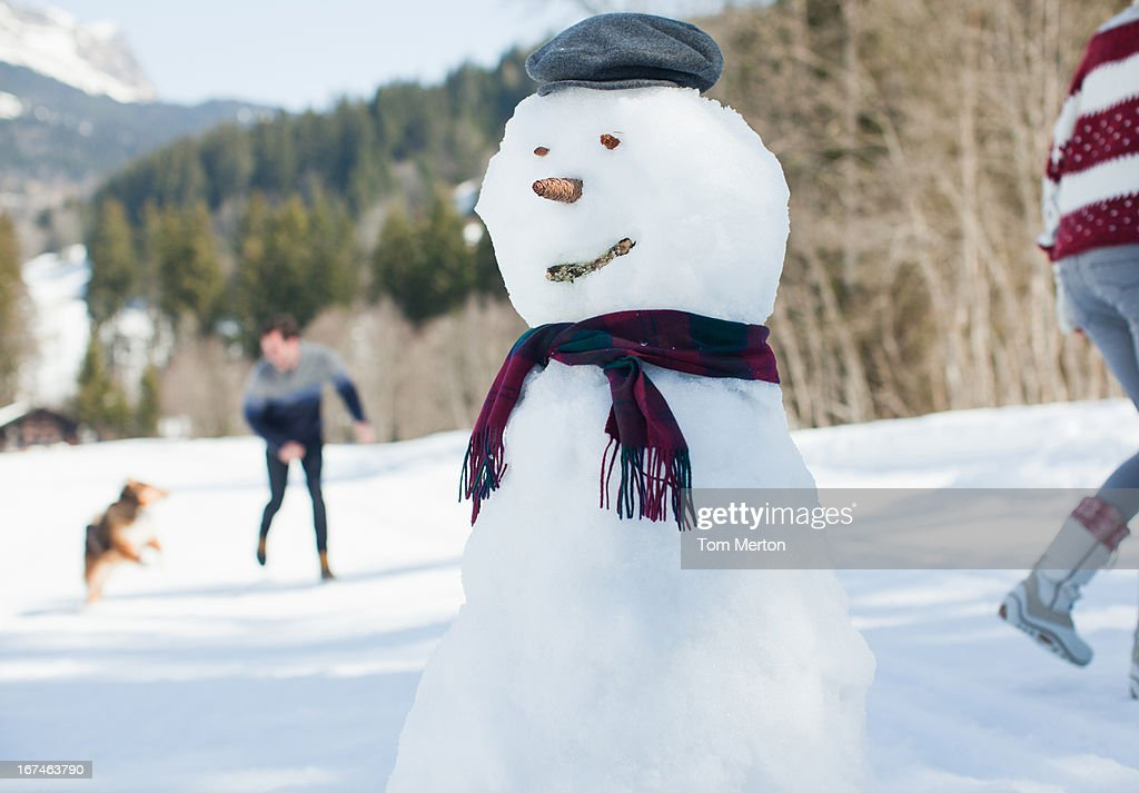 Snowman, people with dog in background : Stock Photo