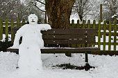 Portrait of a snowman sitting on a park bench