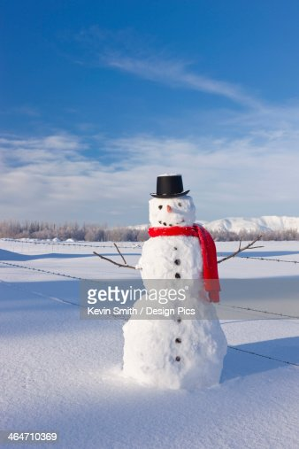 Snowman Wearing A Red Scarf And Black Top Hat Standing In Fresh Snow On A Sunny Day