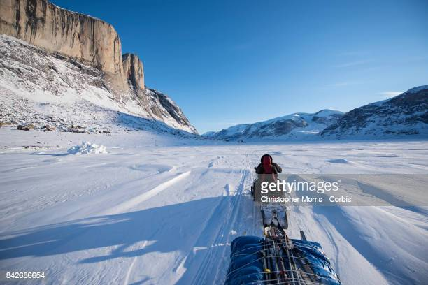 A snowmobile and qamutik crosses the sea ice enroute to Akshayuk Pass in Auyuittuq National Park on April 8 2017 on Baffin Island Canada