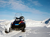Snowmobile and view of peaks