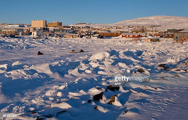 Snowmobiles travel across a frozen Frobisher Bay off Iqaluit Nunavut Canada February 5 2010 as the northern community prepares to host the G7 Finance...