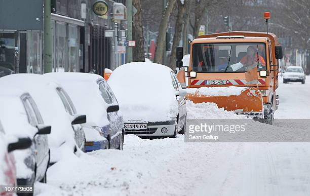 A snowplough clears snow from a street next to snowcovered parked cars on Christmas Day on December 25 2010 in Berlin Germany Snowstorms over the...