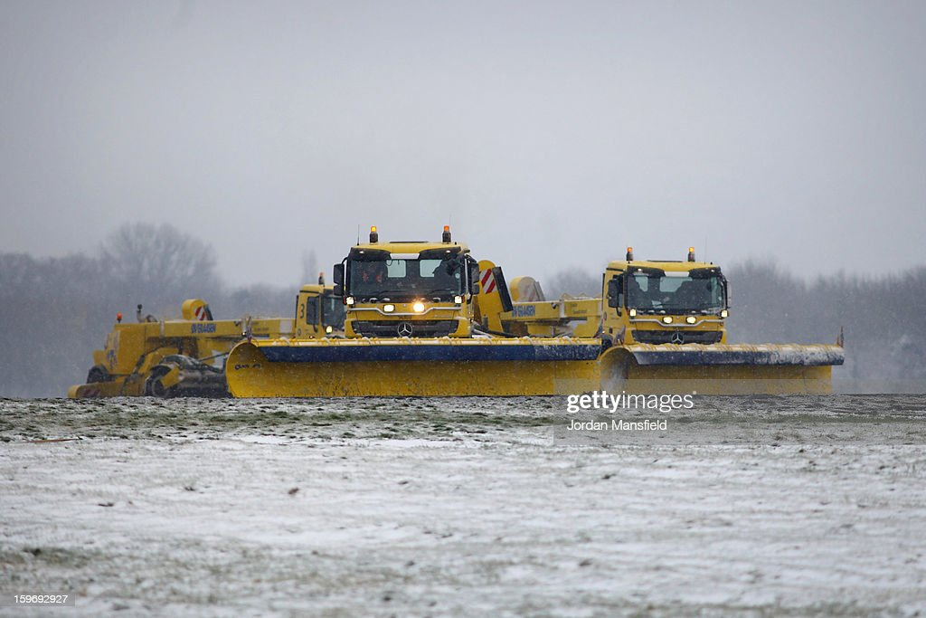 Snow-ploughs clear the runway at Gatwick Airport on January 18, 2013 in London, United Kingdom. Widespread snowfall is affecting most of the UK with school closures and transport disruption. The Met Office has issued a red weather warning for parts of Wales, advising against all non-essential travel as up to 30cm of snow is expected to fall in some areas today.