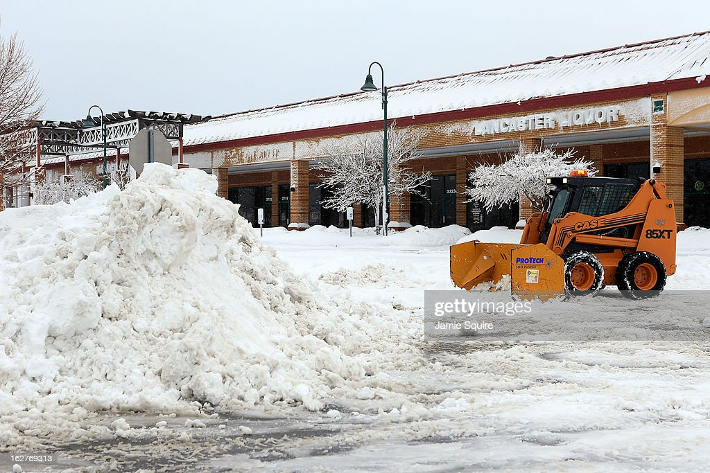 A snowplow helps clear a supermarket parking lot after the area is hit by a snowstorm on February 26, 2013 in Kansas City, Missouri. This is the second major snowstorm the midwest has seen this week dropping a half-foot or more of snow across Missouri and Kansas and cutting power to thousands...