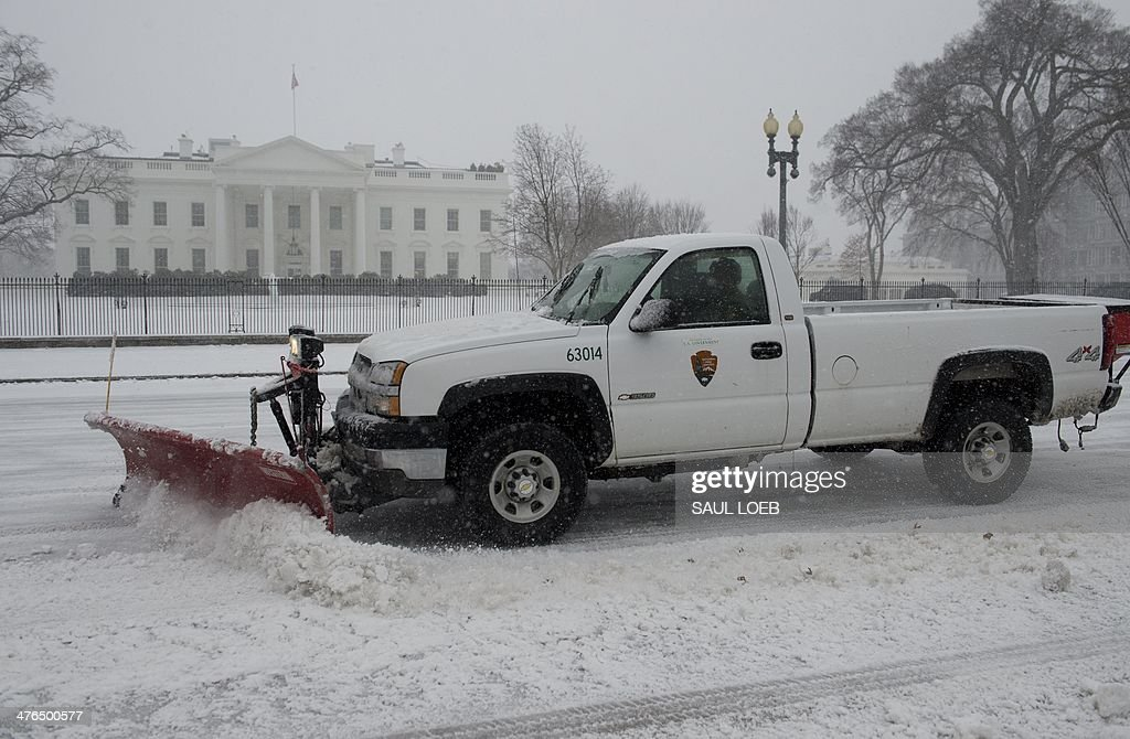 A snowplow moves snow from the street in front of the White House in Washington, DC, March 3, 2014, during a snow storm. Snow began falling in the nation's capital early Monday, and officials warned people to stay off treacherous, icy roads a scene that has become familiar to residents in the Midwest, East and even Deep South this year. Schools were canceled, bus service was halted in places and federal government workers in the DC area were told to stay home Monday. AFP PHOTO / Saul LOEB