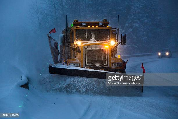 Snowplow plowing the highway during snow storm.