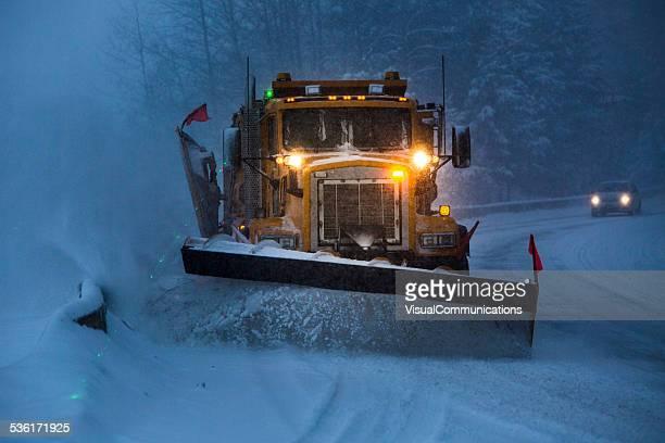 Schneepflug gepflügt der highway während Schnee Sturm.
