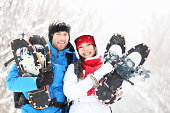 Winter couple happy outdoor hiking in snow on snowshoes. Healthy lifestyle photo of young smiling active mixed race couple snowshoeing outdoors. Asian woman, caucasian man.