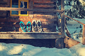 Snowshoes are on the porch of an old log cabin in the warm light of the evening sun. Winter adventure in the wild.