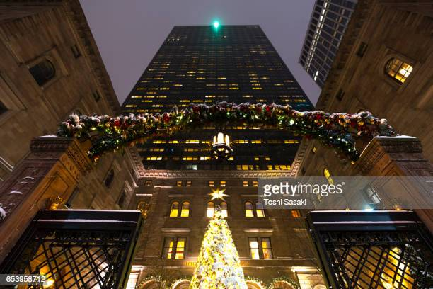 Snowy Christmas tree at New York Palace Hotel in the night at Midtown Manhattan. Christmas tree and courtyard are illuminated and surrounded by Snow.