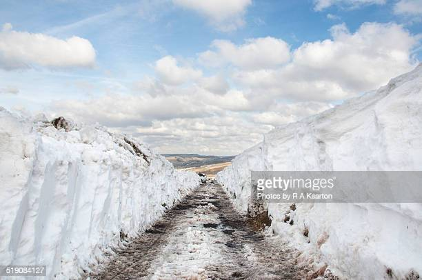Snowy country lane cleared by snowplough
