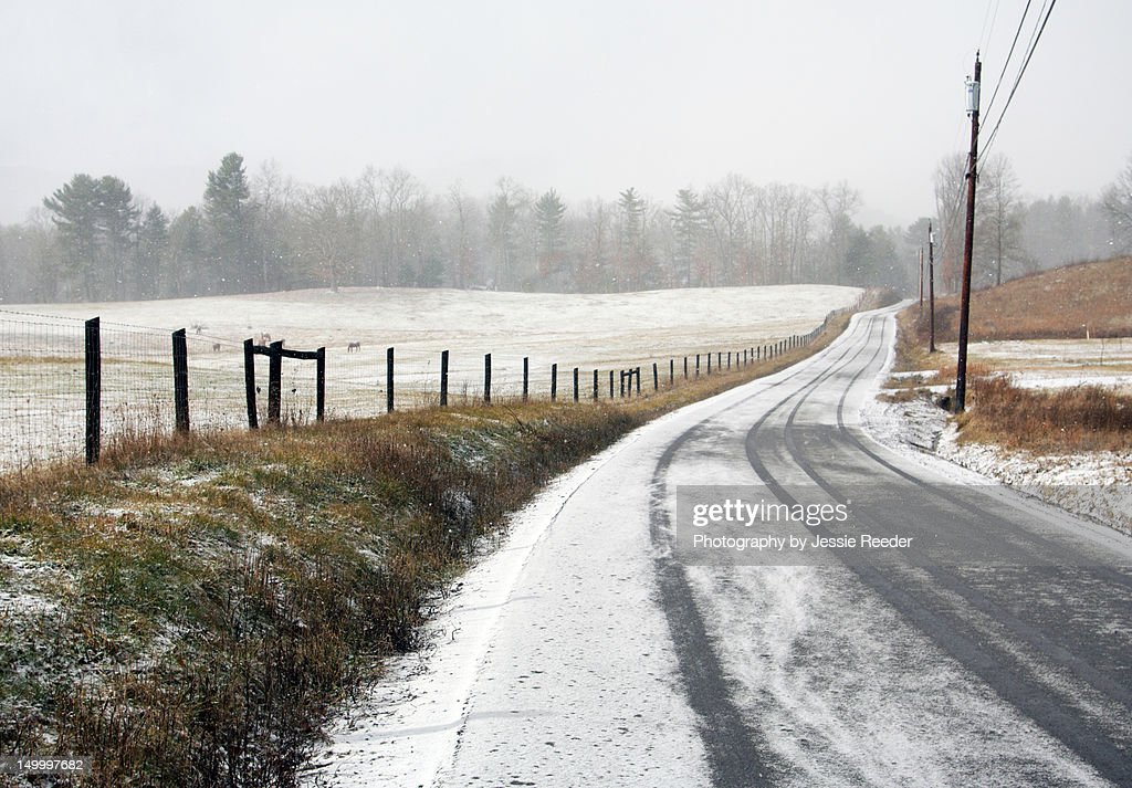 Snowy country road by fence stock photo getty images