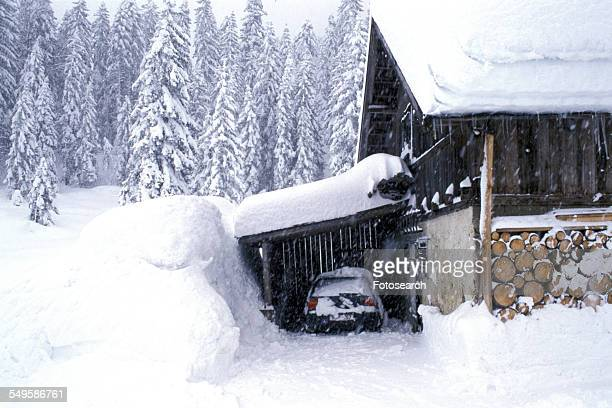 Snowy day at Bavarian cottage with car under shelter