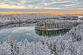 Aerial view of snowy lake and forest at Aulanko nature park in Finland. Late afternoon Sun shining in frozen landscape. HDR image.