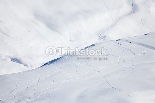 Snowy mountain cowered with curving skiing traces