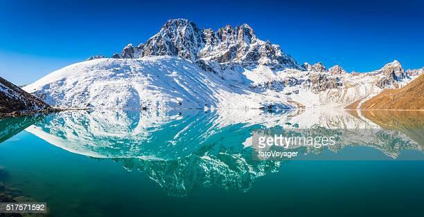 Snowy mountain peaks Phari Lapcha reflecting Gokyo Lake Himalayas Nepal