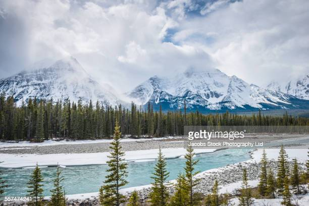 Snowy mountains in forest and remote river, Banff, Alberta, Canada
