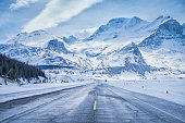 Snowy mountains over field and icy roads