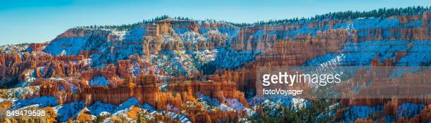 Snowy pine forests golden hoodoo spires Bryce Canyon NP Utah