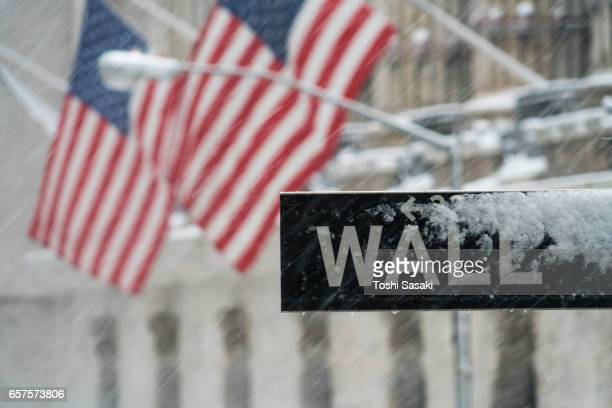 Snowy street sign of Wall Street and American flags during the snowstorm at New York Stock Exchange on Feb. 09 2017.