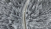 Snowy and frozen winter road with a moving car on it.