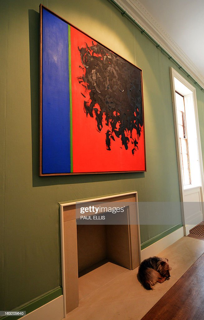 Snugs, the dog of the Duke and Duchess of Devonshire, lies curled up beneath a painting entitled '15-1958' by British artist William Turnbull part of an exhibition in Chatsworth House stately home, in Bakewell, Derbyshire, northern England on March 6, 2013. The Duke and Duchess of Devonshire and the artist's son Alex Turnbull toured installations in the grounds and an exhibition inside ahead of the house opening to the public for the season on March 10. AFP PHOTO / PAUL ELLIS RESTRICTED TO EDITORIAL USE, MANDATORY MENTION OF THE ARTIST UPON PUBLICATION, TO ILLUSTRATE THE EVENT AS SPECIFIED IN THE CAPTION