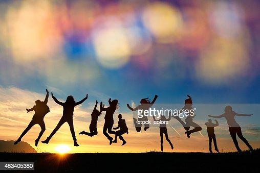 Alors energic amis sautant au coucher du soleil