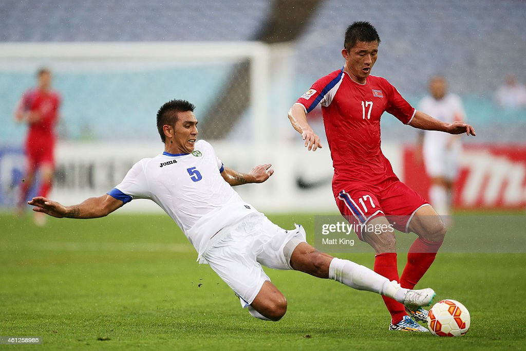 So Hyon Uk of DPR Korea is tackled by Anzur Ismailov of Uzbekistan during the 2015 Asian Cup match between Uzbekistan and DPR Korea at ANZ Stadium on...
